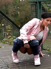 15 pictures - Dark haired girl squats to piss on decking