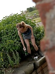 16 pictures - Cute young blondie makes water behind a lush shrub