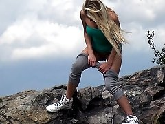 0  - Cute blonde girl stands on rocks to pee outside