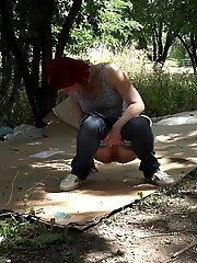 15 pictures - Redhead babe squatting to pee over cardboard