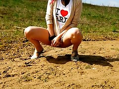 16 pictures - Brunette wets the sand under her feet with her pee